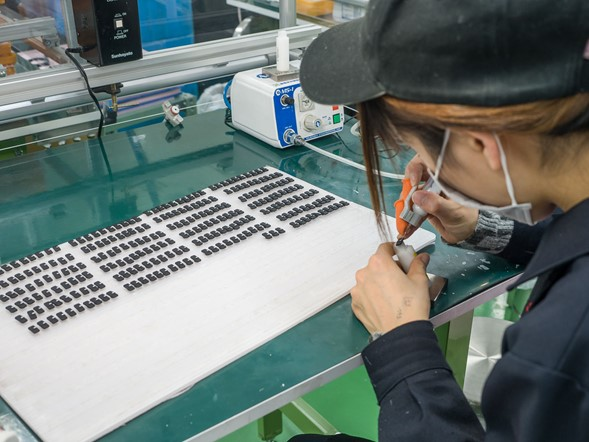 A huge amount of work in the Aizu factory is still done by hand. Here, a worker is hand-painting the white checkmark onto a row of focus mode switches. So next time you use one, spare a thought for the person who does this, for hours every day.
