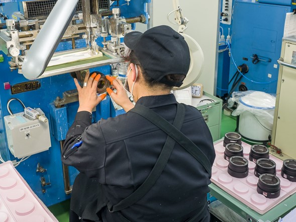 Here, a worker in Sigma's Aizu factory prints lettering onto the barrels of one of the company's lenses, using a silk screening process.