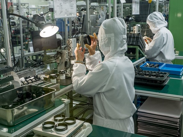 After coating, the lens elements are placed into groups, which are then assembled into the final lens. This shot shows workers checking and assembling lens elements into groups. The elements are held in place initially by friction, inside their TSC trays, before the TSC is heated at the edges and sealed to lock the elements into place. This type of construction replaces the much more involved traditional method where glass elements were held in place by metal bezels screwed tightly into the barrel.